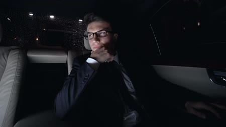 emperrado : Thoughtful businessman waiting in car during traffic jam, busy night city life Vídeos