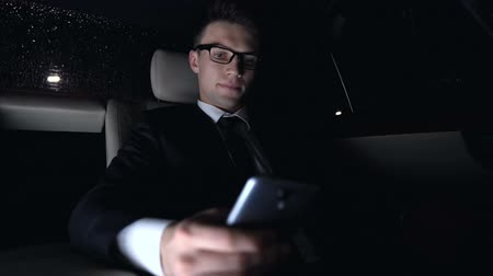 panik : Businessman texting and looking at watch in car, time management failure, late