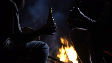 remembering : Men clinking beer bottles, nighttime camping, bonfire flaming and good company Stock Footage