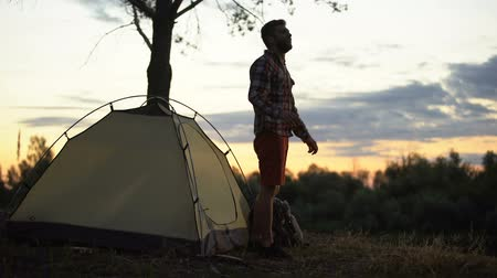tentáculo : Camper getting out of tent in morning, stretching and yawning, admiring scape Stock Footage