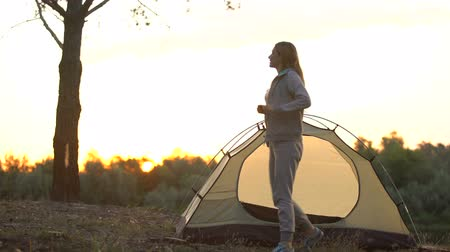 tentáculo : Lady getting out of dome tent and stretching in morning, ready for new adventure