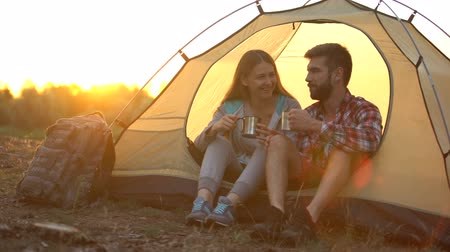 tentáculo : Funny tourists enjoying drink fragrance while sitting in tent, happy together