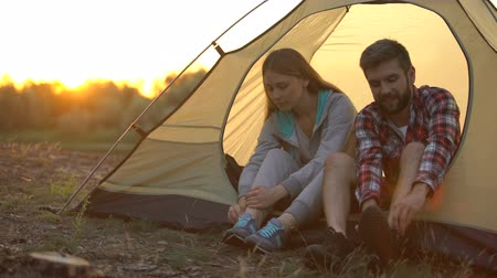 tentáculo : Travelers tying shoelaces while sitting in tent, comfortable shoes for camping