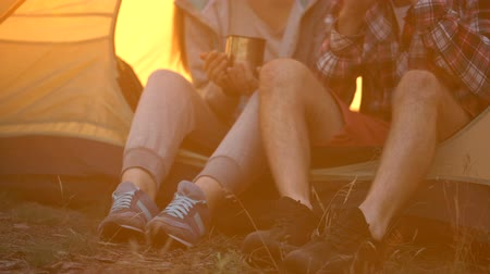 tentáculo : Friends in comfortable shoes sitting in tent and drinking tea, hiking in forest
