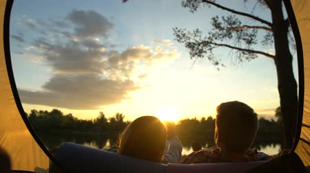 tentáculo : Romantic couple resting and watching sunset near tent, girl holding mans hand