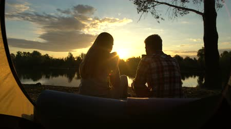 tentáculo : Man and woman drinking alcohol on bank of river, careless lifestyle, holidays.