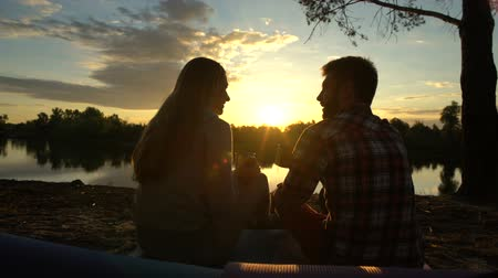 descuidado : Carefree couple toasting and drinking alcohol on river bank, picturesque view Vídeos