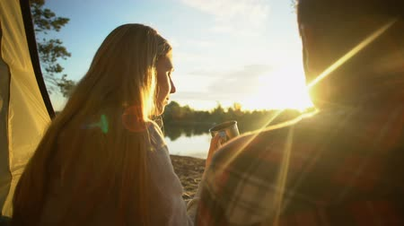 tentáculo : Couple drinking water and watching beautiful sunset in tent, discussing relation