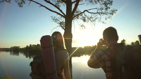 遠足 : Backpackers taking photo of gorgeous scape, beautiful river and sunset view 動画素材