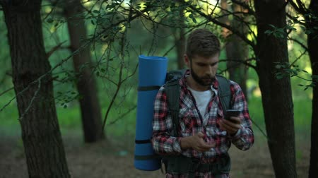 ориентация : Camper searching for mobile phone signal after lost in woods, bad connection