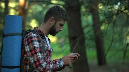 ориентация : Male lost in forest using compass to navigate, finding way out from woods