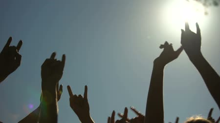aperto cartello : Raised hands showing rock sign of the horns gesture, rock concert, party time Filmati Stock