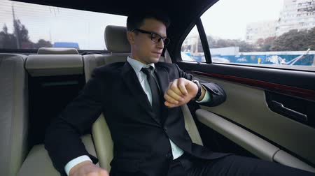 emperrado : Businessman looking at watch late for meeting stuck in traffic jam in luxury car