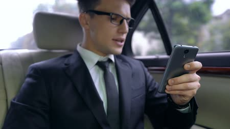 unsuccessful : Anxious young man in suit receiving message with bad news, ride in luxury auto