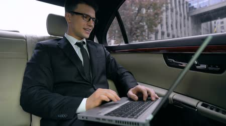 восхищенный : Smiling businessman reading good news on laptop, yes gesture on backseat of car