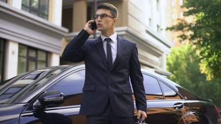 subordinate : Irritated young male in formalwear talking on phone, annoyed by problems Stock Footage