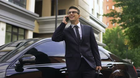 berlina : Happy smiling male in suit receiving good news near expensive sedan. Filmati Stock