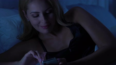 weboldal : Pretty woman typing message in smartphone, relaxing in bed, social network