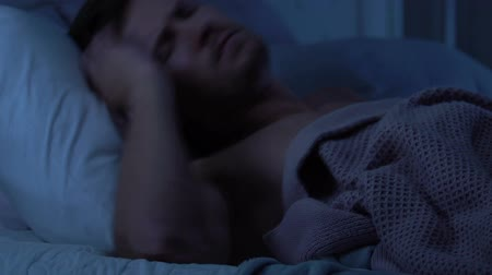 deprivation : Man trying to sleep, disturbed by street noise or loud neighbor talks, insomnia Stock Footage