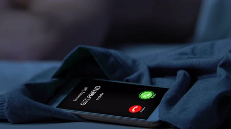 входящий : Missed call from girlfriend, man sleeping on background, suspicion and jealousy Стоковые видеозаписи