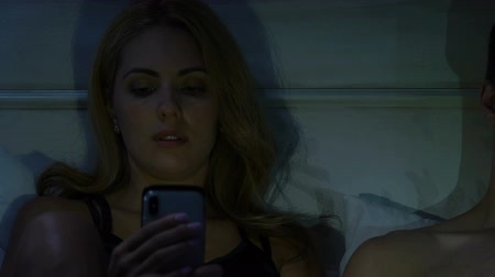 meghittség : Couple lying in bed playing smartphones instead of intimacy, gadget addiction