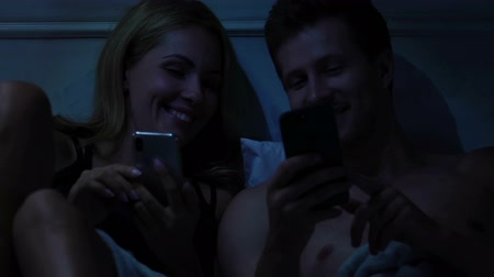 harcama : Cheerful couple spending time in bed, choosing vacation tour on smartphones