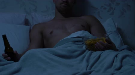 ленивый : Bachelor spending evening in bed watching TV, drinking beer and eating snacks