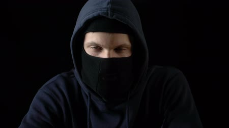 felon : Hooded serious criminal in balaclava looking at camera, piercing glance, concept