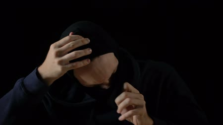 balaclava : Mad criminal taking off balaclava mask after committing crime, black background Stock Footage