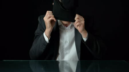 rabló : Male in suit putting on balaclava, government corruption, black background