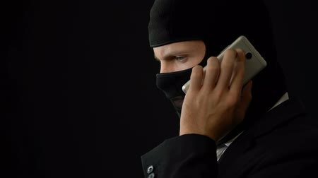 balaclava : Killer in balaclava talking on phone, holding gun and planning crime, corruption