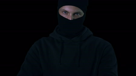 overval : Silhouette of criminal in balaclava aiming gun armed robbery, black background Stockvideo