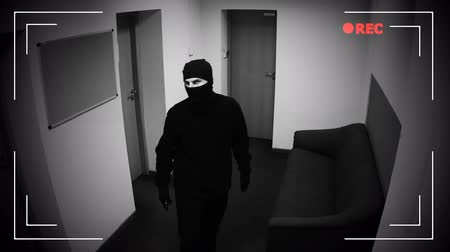 delinquant : Man in balaclava hacking CCTV camera in corporative building, error grey screen Vidéos Libres De Droits
