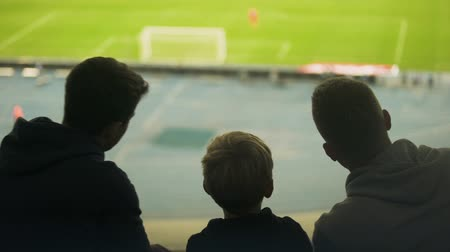 otcovství : Father and two sons watching football match together, happy weekend, fatherhood