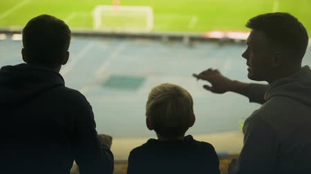 trest : Boy with brothers emotionally watching football at stadium, excited with game