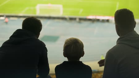 審判 : Boy with family watching football match, discussing referee or missed goal