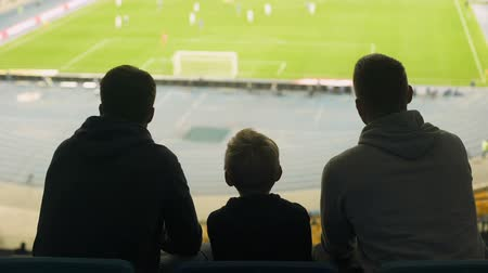 penas : Male supporters and child watching football match at stadium, discussing game