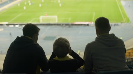 penas : Male fans with child watching football at stadium, keep silent, disappointed