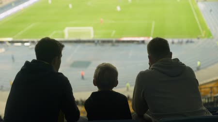 penas : Male friends with kid quietly watching football at stadium, boring game, defeat Stock Footage