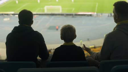 penas : Anxious football fans with kid watching game at stadium, frustrated with defeat Stock Footage