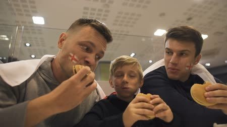 sports nutrition : English football fans eating burgers after match, harmful effect of fast food