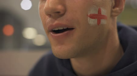 extremely : Football fan with English flag painted on cheek watching match enthusiastically