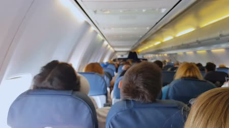 assentos : People travelling in small uncomfortable airplane seats, low cost airlines Stock Footage