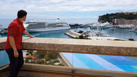 billionaire : Tourist staying on terrace of luxury hotel and observing sea port with yachts