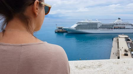 задумчивый : Tourist admiring seascape with cruise liner, comfortable travel by sea transport