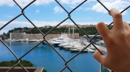social inequality : Man views yachts behind fence, corrupt official looks at confiscated property Stock Footage