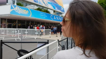 гласность : Female fan waiting for idol behind fence, International Cannes festival, closeup