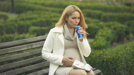 snoepen : Irresponsible expectant drinking unhealthy soft drink on bench, baby health care