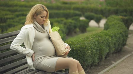 antecipação : Blond expecting lady resting bench holding grocery bag, pregnancy difficulties