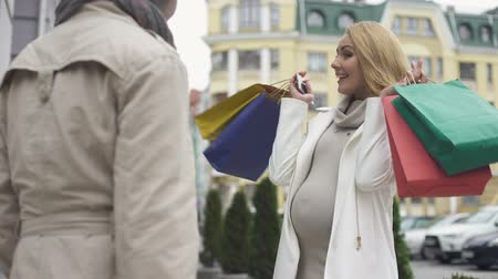 expectativa : Smiling mother-to-be showing shopping bags to friend, childbirth purchase, sale Vídeos